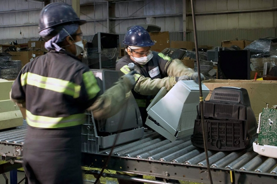 Workers in protective gear handle recycled products as they move down a conveyor line