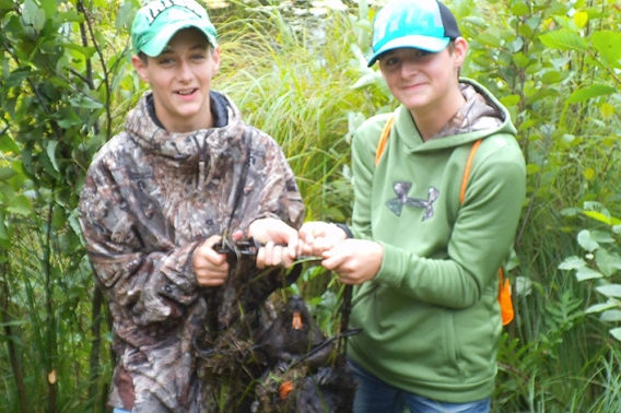 Two young men with a trapped beaver.