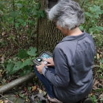 A snapshot volunteer setting up her trail camera